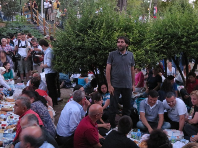 This man stood up to say a Muslim prayer, after which people started to eat together.