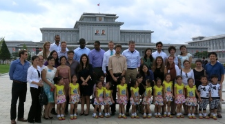 A group photo  in front of the Kim Il-Sung and Kim Jong-Il mausoleum. The cute kids in yellow were there to take photos with tourists