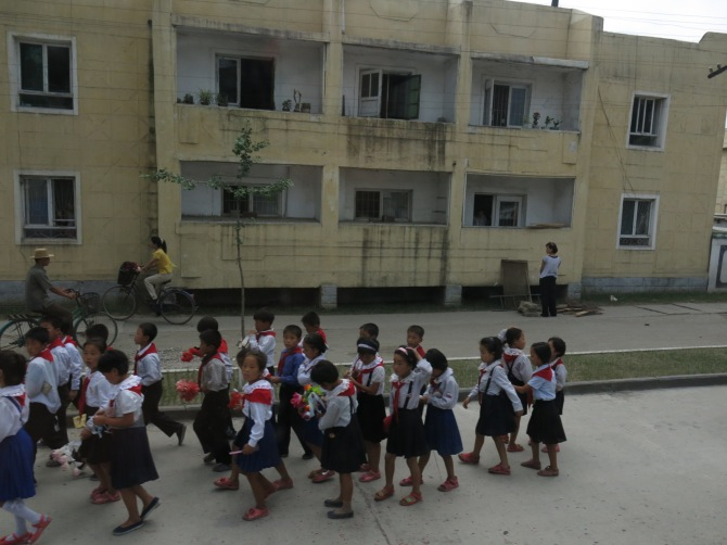 Little students in Wonsan, North Korea (took this photo from our bus)
